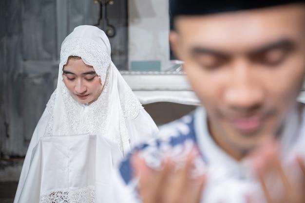 Aziatische moslim man en vrouw bidden samen jamaah thuis