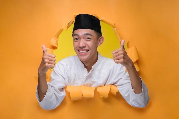 Aziatische moslim man glimlachend en duimen opdagen poses door gescheurd geel papier gat, moslim doek met schedeldak dragen.