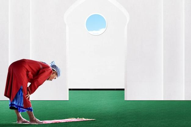 Aziatische moslim man in biddende positie (salat) op de moskee