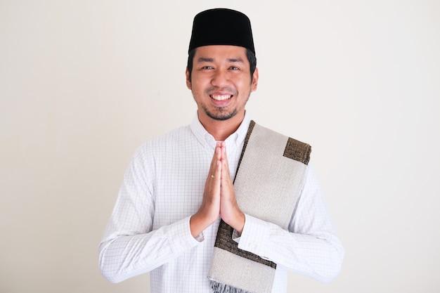 Aziatische moslim man lacht en geeft een vriendelijke groet