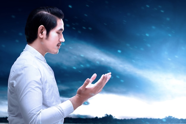 Aziatische moslim man permanent terwijl opgeheven handen en bidden met dramatische hemelachtergrond