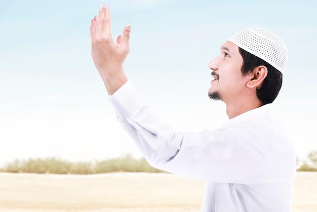 Aziatische moslim man permanent terwijl opgeheven handen en bidden met een blauwe hemelachtergrond