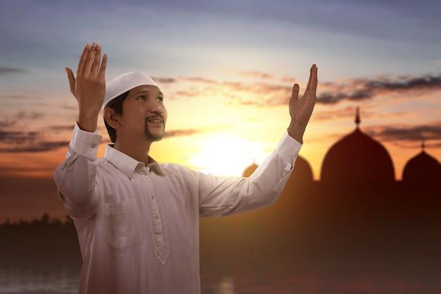 Aziatische moslim man permanent terwijl opgeheven handen en bidden