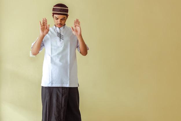 Aziatische moslim man salat met het opheffen van zijn hand of takbiratul ihram met kopie ruimte
