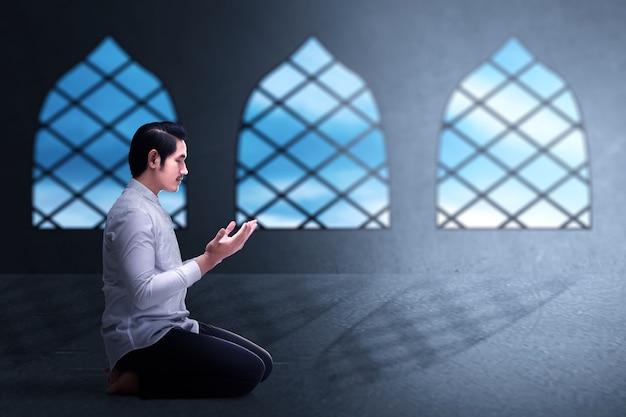 Aziatische moslim man zittend terwijl opgeheven handen en bidden op de moskee