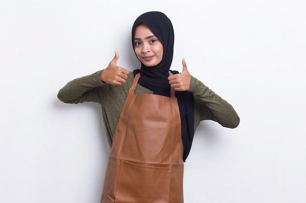 Aziatische moslim vrouw barista serveerster dragen schort met ok teken gebaar tumb omhoog geïsoleerd op wit