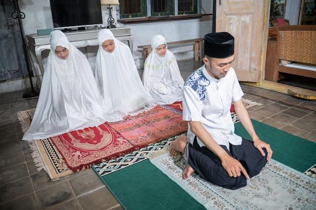 Aziatische moslimfamilie die jamaah samen thuis bidt. sholat of salah in wit en hijab