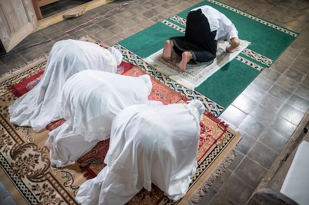 Aziatische moslimfamilie die thuis jamaah bidt