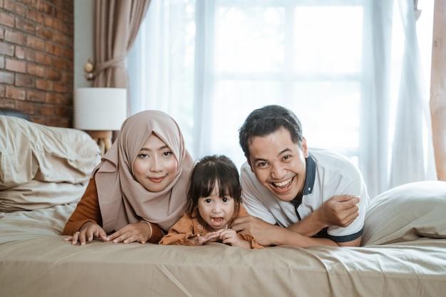 Aziatische moslimfamilies lachen vrolijk als ze naar de camera kijken