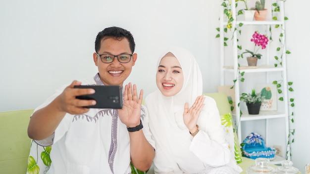 Aziatische moslimgezinnen vieren samen eid tijdens videogesprekken