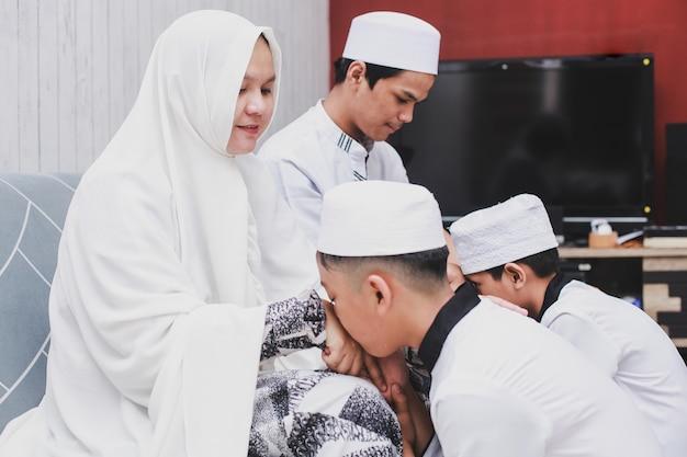 Aziatische moslimjongens die ouders kussen in het huis op eid mubarak