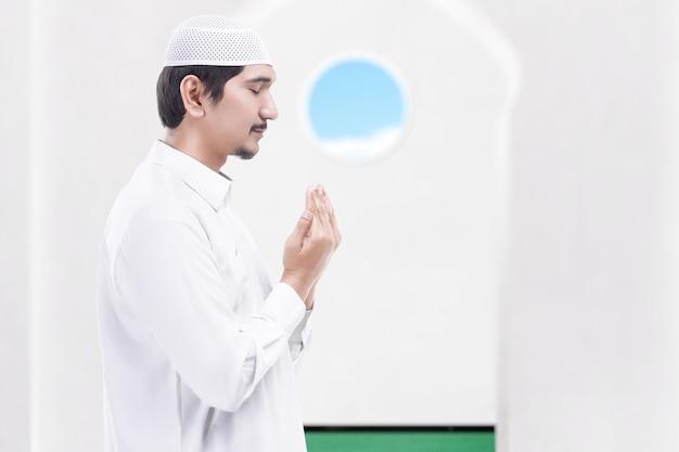 Aziatische moslimman die staat terwijl hij zijn handen opsteekt en bidt op de moskee