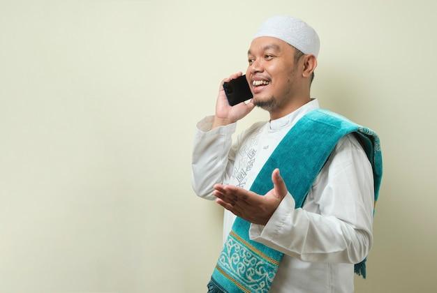 Aziatische moslimman ziet er blij uit als hij een telefoontje krijgt van zijn broer