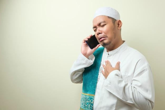 Aziatische moslimman ziet er verdrietig uit als hij nieuws van zijn smartphone ontvangt