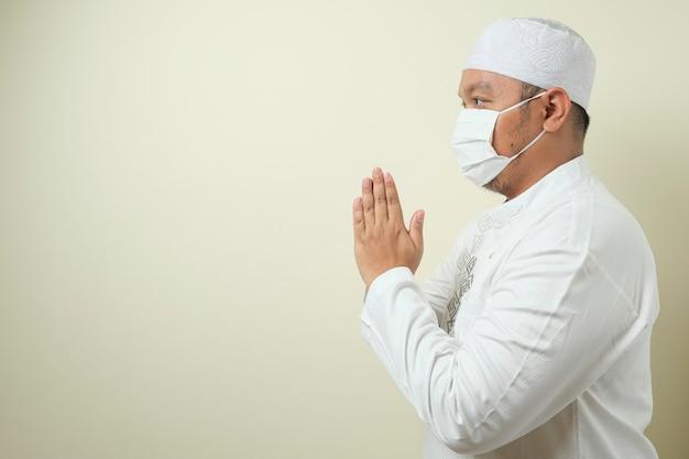 Aziatische moslimmannen die masker dragen met gebaren van groeten aan gasten