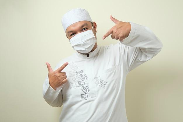 Aziatische moslimmannen die maskers dragen met zelfverzekerde gebaren duimen omhoog en wijzen naar de maskers