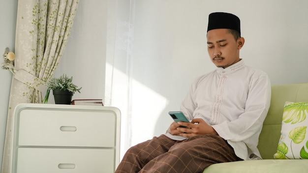 Aziatische moslimmannen die op de bank zitten en bezig zijn met hun telefoons in de woonkamer tijdens eid thuis