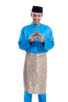 Aziatische moslimmens met mobiele telefoon die koko melayu dragen die over wit wordt geïsoleerd