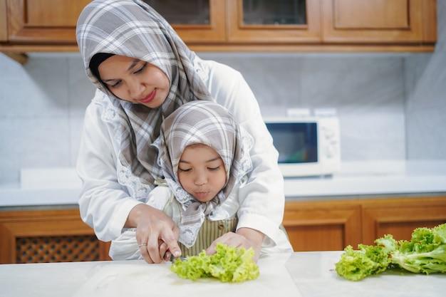 Aziatische moslimmoeder bereidt een gezonde groene salade voor en geniet van koken