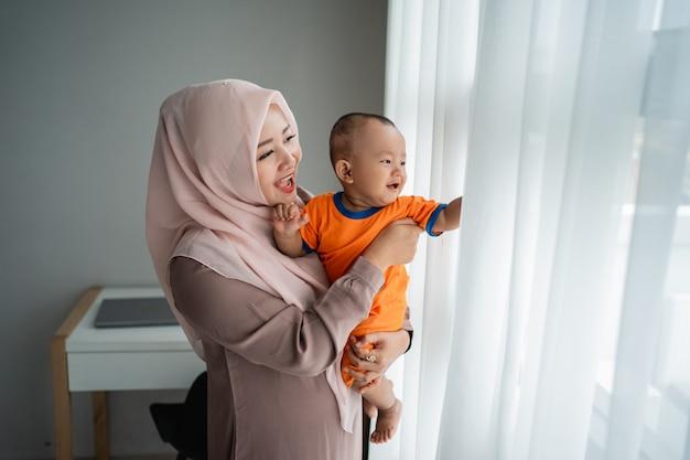 Aziatische moslimmoeder die haar kleine jongen vervoert wanneer het spelen dichtbij venster