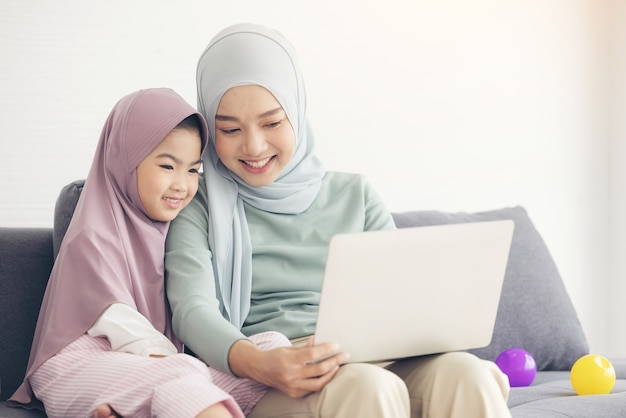 Aziatische moslimmoeder en dochter die bij het samen gebruik van laptop glimlachen