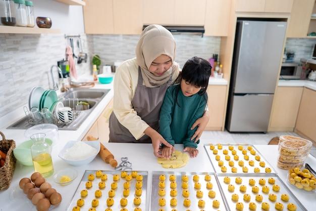 Aziatische moslimmoeder en dochter die thuis in de keuken samen een nastartaart maken