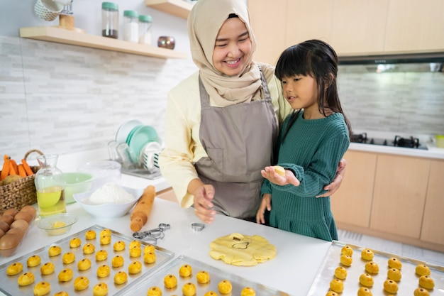 Aziatische moslimmoeder en haar dochter die thuis in de keuken samen een nastartaart maken