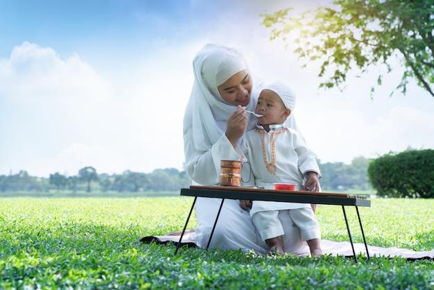 Aziatische moslimmoeder en haar zoon die kwaliteits van tijd genieten bij park, moslimmamma en zoonconcept