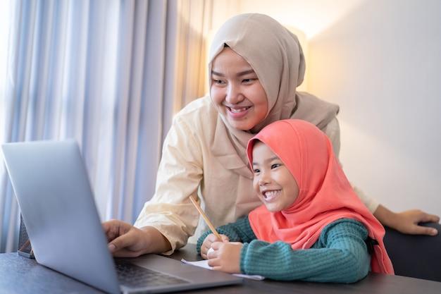 Aziatische moslimmoeder helpt haar dochter om online te leren met behulp van laptop thuis studeren