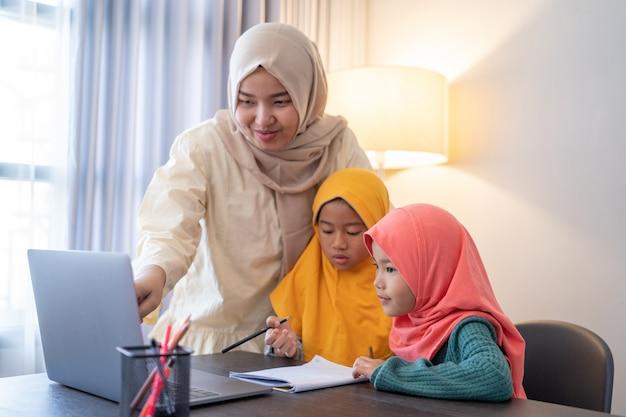 Aziatische moslimmoeder helpt haar dochter om 's avonds tijdens thuisonderwijs te studeren