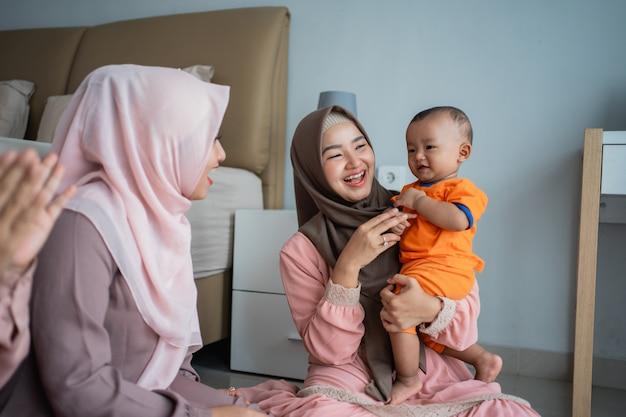 Aziatische moslimmoeder met haar vrienden spelen graag met haar zoon wanneer ze op de grond zit