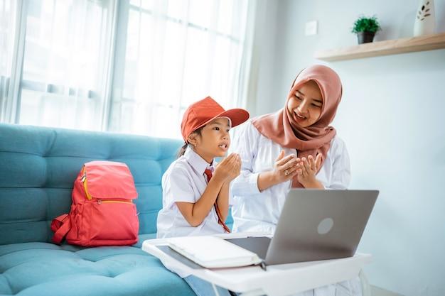 Aziatische moslimstudent die bidt voordat ze haar online les vanuit huis begint