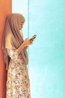 Aziatische moslimstudent gebruikt mobiele telefoon