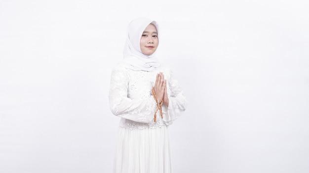 Aziatische moslimvrouw die de gastvrije gasten van gebedparels draagt