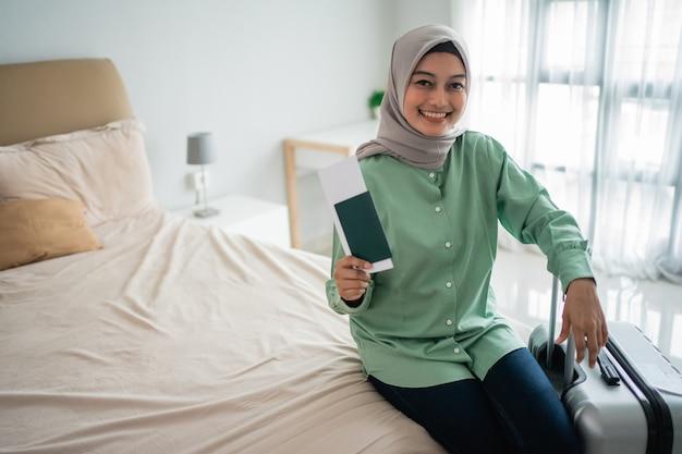 Aziatische moslimvrouw die een kaartje en een koffer houdt