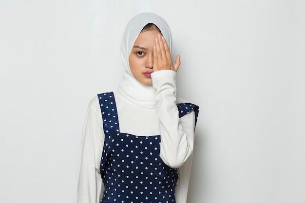 Aziatische moslimvrouw die één oog met de hand bedekt