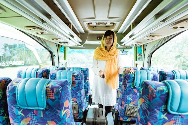 Aziatische moslimvrouw die eid mubarak doet die terug naar haar geboorteplaats reist door een bus te berijden
