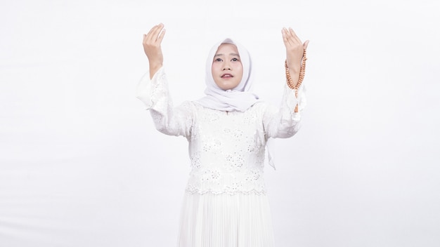 Aziatische moslimvrouw die gebedparels draagt bidt in wit