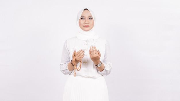Aziatische moslimvrouw die gebedparels draagt bidt in witte ruimte