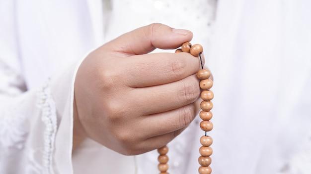 Aziatische moslimvrouw die gebedparels draagt, bidt met tasbih in het wit