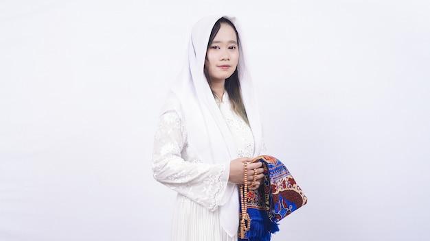Aziatische moslimvrouw die gebedparels en gebedsmat in wit draagt