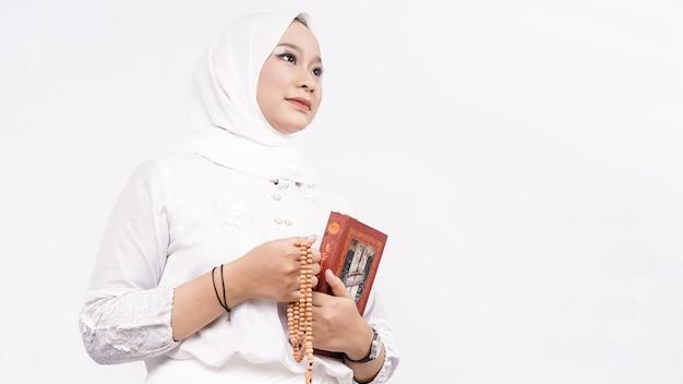 Aziatische moslimvrouw die gebedsparels draagt, bidt met tasbih en koran in witte ruimte