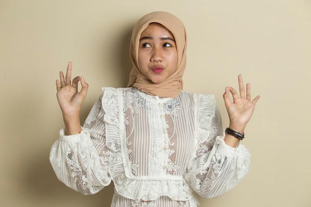 Aziatische moslimvrouw die hijab met ok tekengebaar draagt
