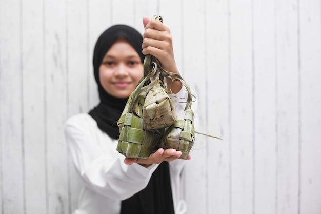Aziatische moslimvrouw die ketupat toont voor de viering van eid mubarak