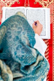 Aziatische moslimvrouw die koran of koran bestudeert