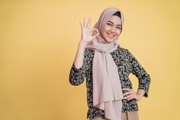 Aziatische moslimvrouw die lacht met een goed goedkeurend handgebaar bij het kijken naar de camera