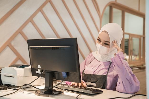 Aziatische moslimvrouw die met behulp van pc werkt terwijl ze een medisch gezichtsmasker draagt voor bescherming op kantoor