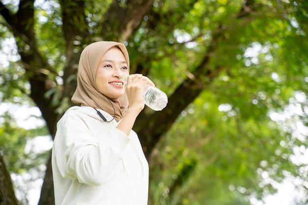 Aziatische moslimvrouw die met hoofddoek een fles water drinkt tijdens het sporten buiten
