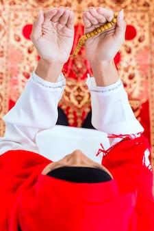 Aziatische moslimvrouw die met parelsketen bidt