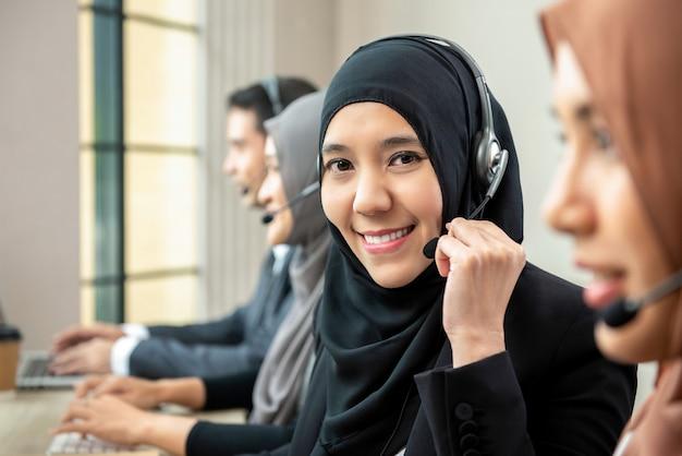 Aziatische moslimvrouw die microfoonhoofdtelefoons dragen die met team in call centre werken